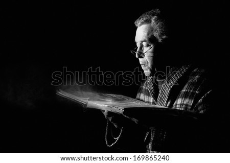 Senior man blowing dust of  a very old book in black & white - stock photo