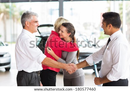 senior man buying car for his daughter handshaking with dealer after the sale - stock photo