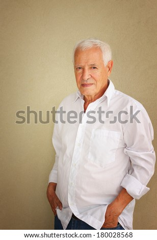 senior man casually leaning against textured wall