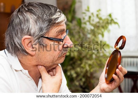 Senior man checking his double chin in mirror. - stock photo