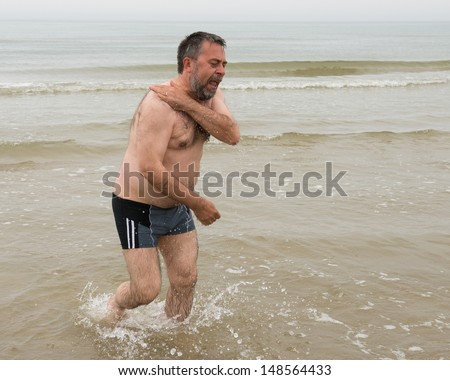 Senior man comes out of cold Baltic Sea