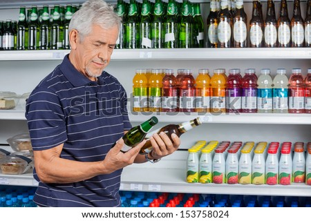 Senior man comparing beer bottles at supermarket