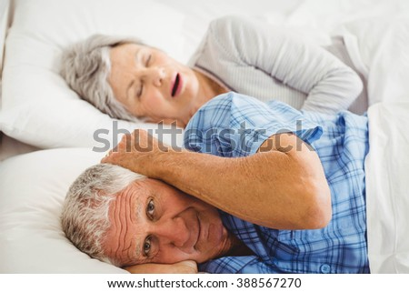 Senior man covering her ears while man snoring in bed - stock photo