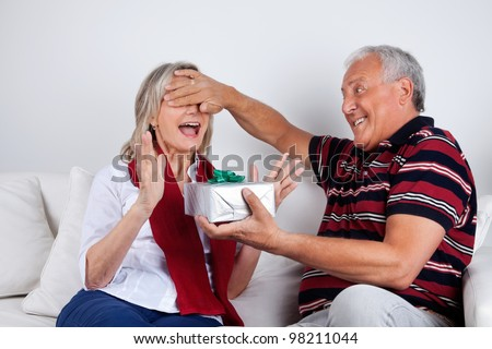 Senior man covering his wife's eyes to surprise her with a gift - stock photo