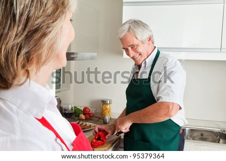 Senior man cutting pepper for cooking in kitchen - stock photo