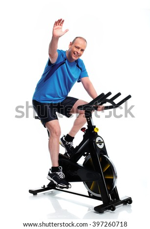 Senior Man cycling on bike trainer. - stock photo