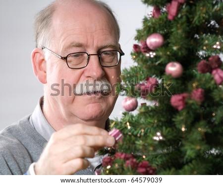 Senior man decorate Christmas tree - stock photo