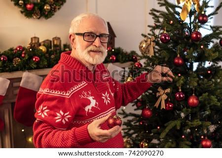 https://thumb1.shutterstock.com/display_pic_with_logo/167881400/742090270/stock-photo-senior-man-decorating-christmas-tree-with-christmas-balls-742090270.jpg