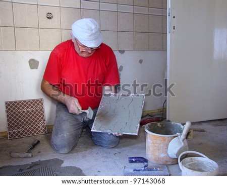 Senior Man decorating with ceramic tiles - stock photo