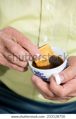 Senior man dips a cookie in his coffee - stock photo