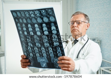 Senior man doctor examines MRI image of human head in hospital - stock photo