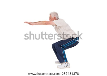 Senior man doing a squat on white background - stock photo