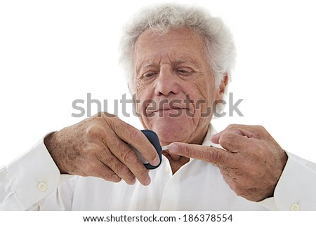 Senior man doing blood sugar test at home  - stock photo