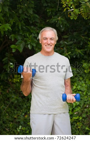 Senior man doing his exercises in the garden - stock photo