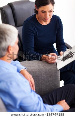 senior man doing Rorschach inkblot test with his therapist in office - stock photo