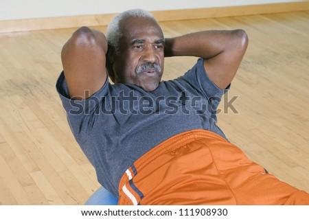 Senior man doing sit-ups on a pilates ball - stock photo