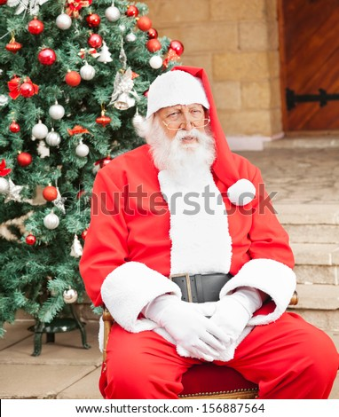 Senior man dressed as Santa Claus sitting in front of Christmas tree outside house - stock photo