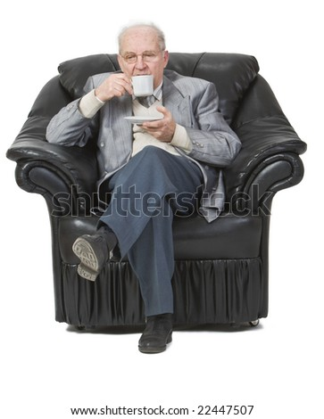 Senior man drinking coffee while is sitting in an armchair. Soft Focus - stock photo