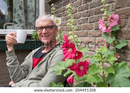 senior man drinks coffee in garden with hollyhocks - stock photo
