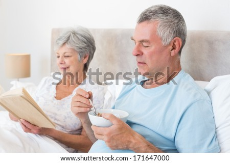 Senior man eating cereals while wife reading book in bed at home - stock photo