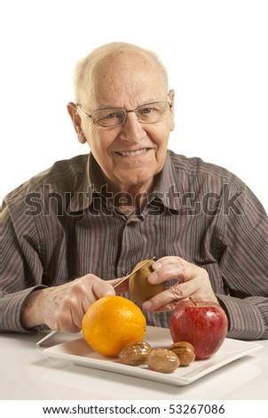Senior man eating fresh fruit isolated on white - stock photo