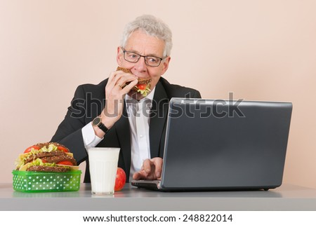 Senior man eating with lunch box and working with laptop at the office