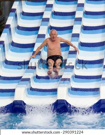 Senior man enjoying holiday in aqua park - stock photo