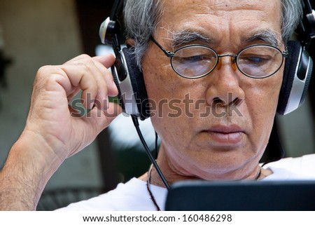 Senior man enjoying music on his tablet. - stock photo