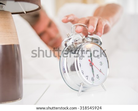 Senior man exclude the alarm clock in the morning. - stock photo