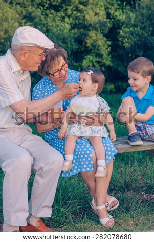 Senior man feeding with fruit puree to adorable baby girl sitting over a senior woman in a bench outdoors. Grandparents and grandchildren lifestyle concept. - stock photo
