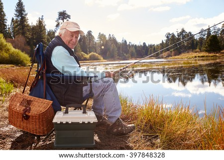 Senior man fishing in a lake, looking to camera, California - stock photo
