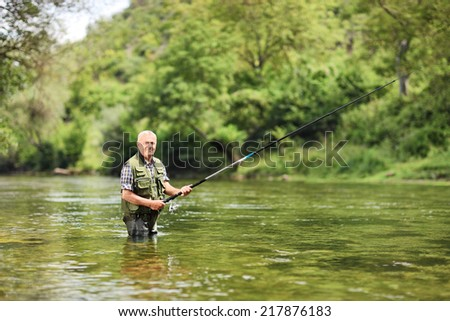 Senior man fishing in a river on a sunny summer day