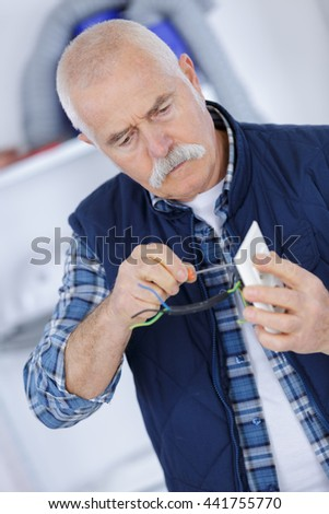 senior man fixing electric plug