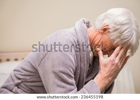 Senior man getting a headache at home in bedroom - stock photo