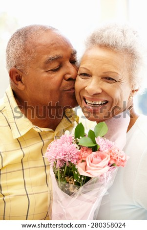 Senior man giving flowers to wife - stock photo