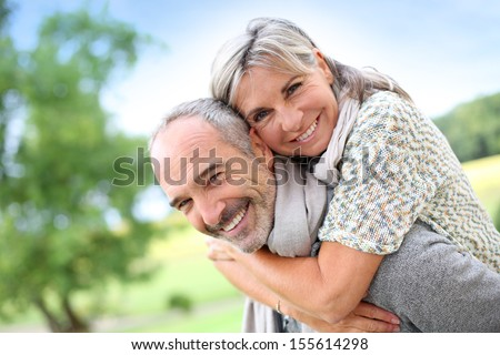 Senior man giving piggyback ride to woman - stock photo