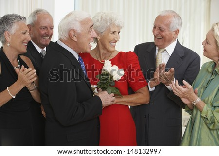 Senior man giving wife bouquet of flowers while friends clapping