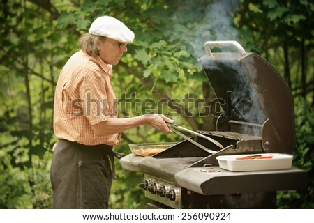 Senior man grilling outdoors. Smoke rises from the barbecue. The picture is desaturated and has been treated with digital filters