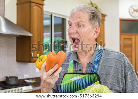 Senior man having fun in kitchen with healthy food - Retired people holding carrot, yellow bell pepper and cooking meal at home with vegetables - Happy elderly concept