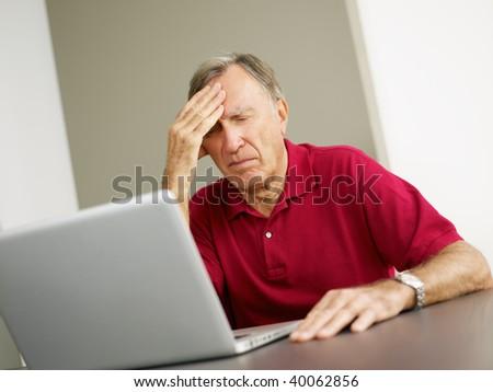 Senior man having headache while using laptop. Copy space - stock photo