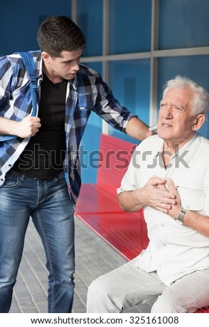 Senior man having heart infarct at the bus stop - stock photo