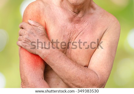 Senior man having shoulder pain, photo with red as a symbol for the hardening - stock photo