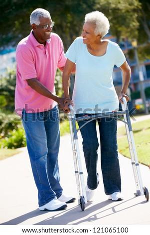 Senior Man Helping Wife With Walking Frame - stock photo