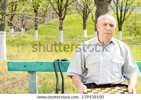Senior man holding a chessboard and sitting outdoors