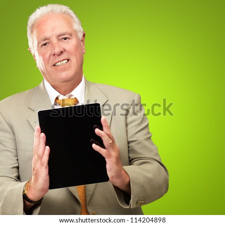 Senior Man Holding A Digital Tablet On Green Background - stock photo