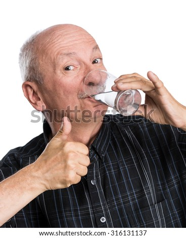 Senior man holding a glass of water and giving a thumb up on a white background