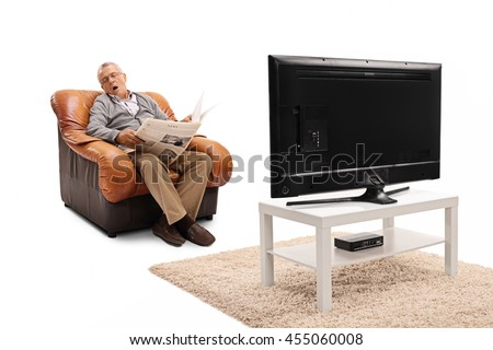 Senior man holding a newspaper and sleeping in front of the TV isolated on white background