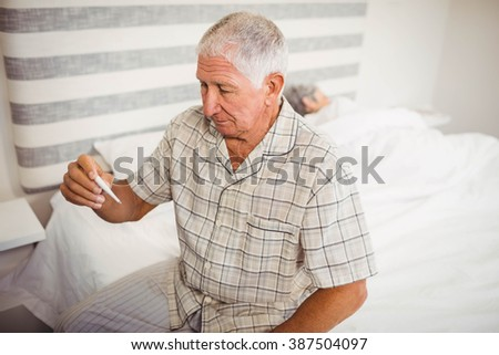 Senior man holding a thermometer in bedroom