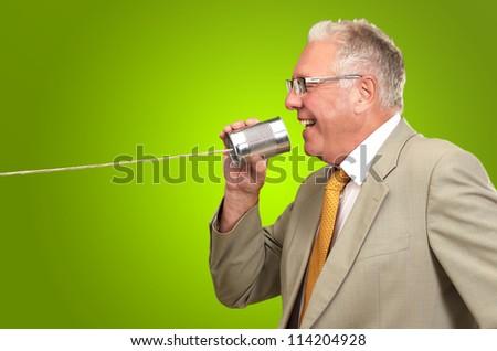 Senior Man Holding A Tin On Green Background - stock photo