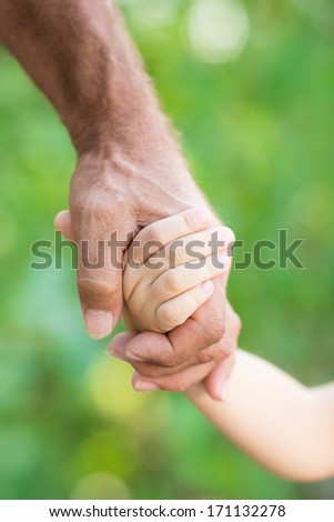 Senior man holding baby by the hands outdoors - stock photo
